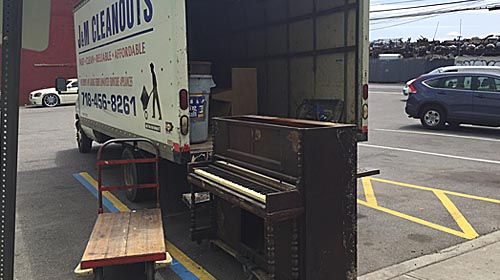 Unwanted piano being loaded on a hauling truck in New York City